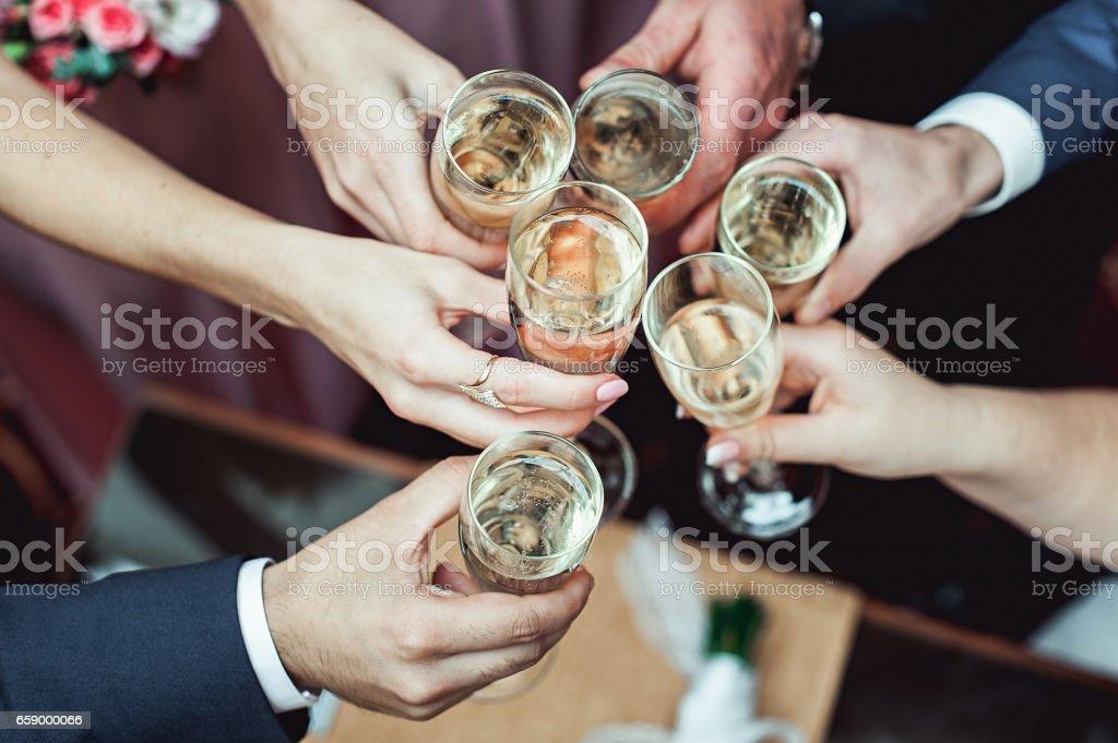 Personas se mantienen en los vidrios de las manos con vino blanco. Fiesta de la boda. - foto de stock
