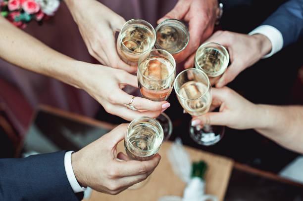 Personen in Händen Gläser mit Weißwein ablöschen. Hochzeitsgesellschaft. – Foto