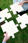istock People hold large jigsaw pieces that symbolize teamwork 175519540
