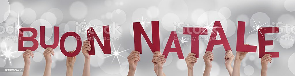 People Holding Buon Natale on Silver Backgound royalty-free stock photo