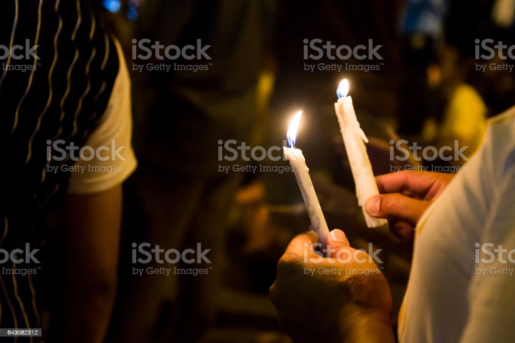 People holding candle vigil in darkness stock photo