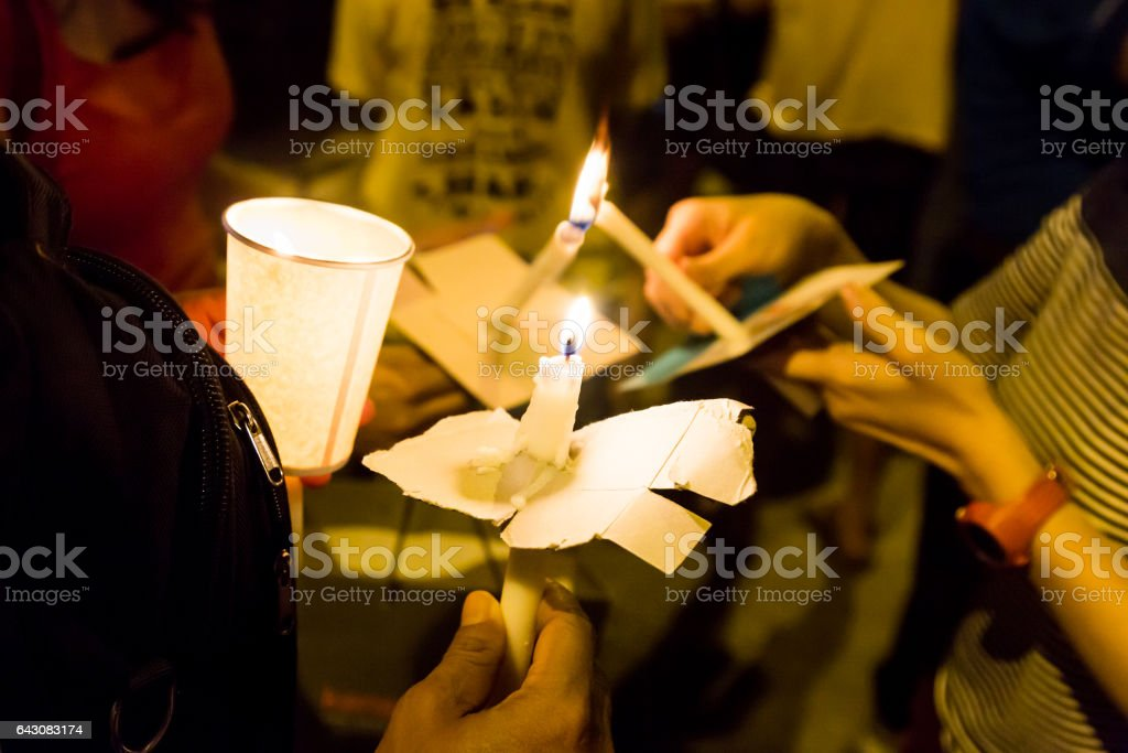 People holding candle vigil in darkness seeking hope, worship, prayer stock photo
