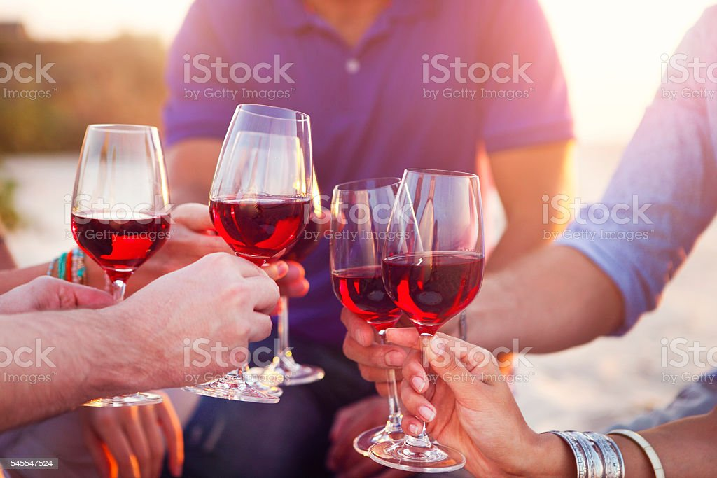 People holding glasses of red wine toast at beach stock photo