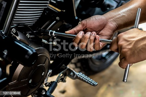 Image is close up. People holding hand are repairing a motorcycle Use a wrench and a screwdriver to work.