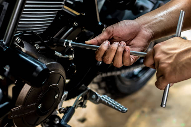 People holding hand are repairing a motorcycle. Image is close up. People holding hand are repairing a motorcycle Use a wrench and a screwdriver to work. motorcycles stock pictures, royalty-free photos & images