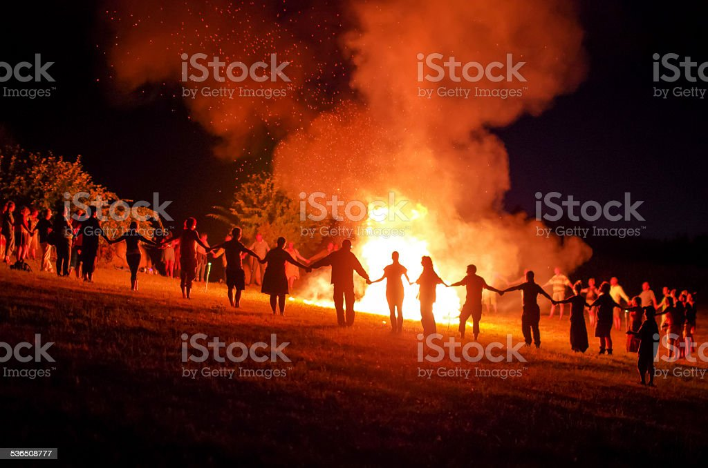 People holding hands around a fire stock photo