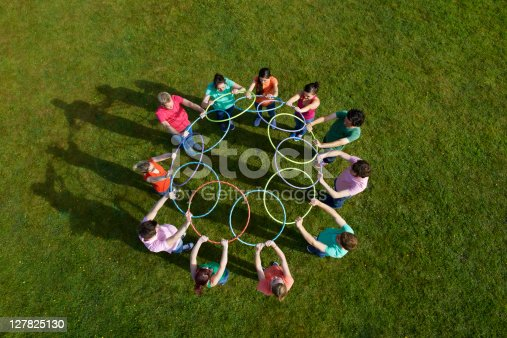 istock People holding hula hoops in circle 127825130