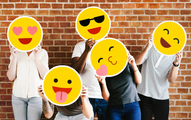 people holding positive emoticons - emoji foto e immagini stock