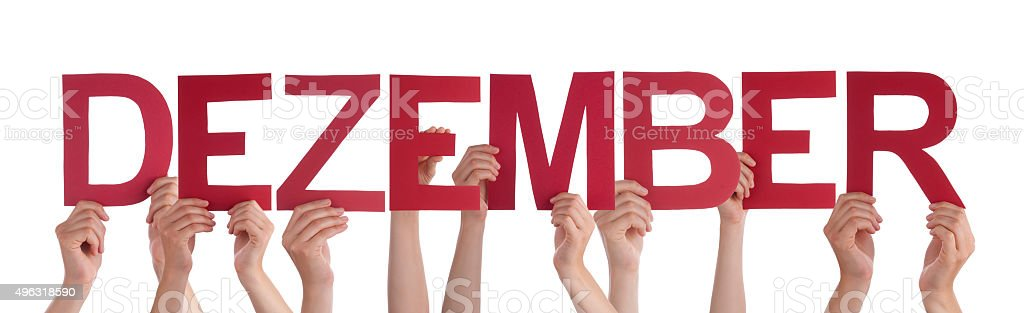 People Holding Straight German Word Dezember Means December stock photo