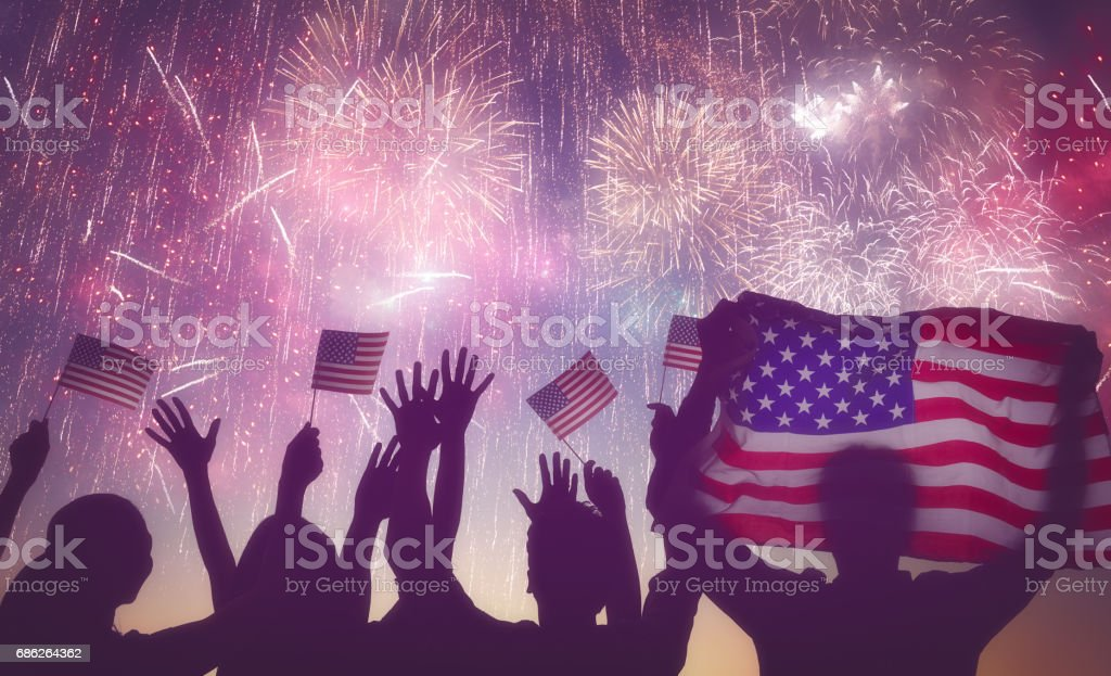 people holding the Flag of USA Patriotic holiday. Silhouettes of people holding the Flag of USA. America celebrate 4th of July. Adult Stock Photo