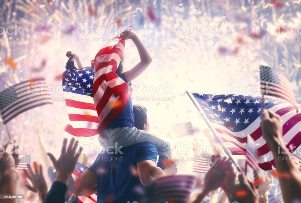People holding the Flags of the USA. stock photo