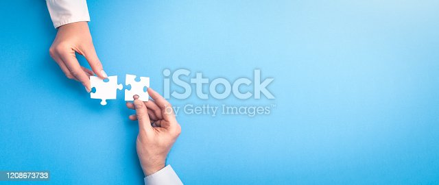 istock People holds in hand a jigsaw puzzle. Business solutions, success and strategy. 1208673733