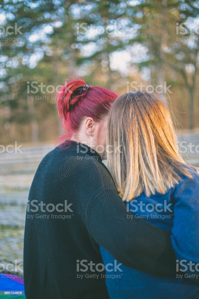 people, homosexuality, gay and love concept - close up of happy lesbian couple holding hands over rainbow flag royalty-free stock photo