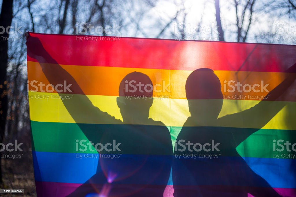 people, homosexuality, , gay and love concept - close up of happy male gay couple hands over rainbow flag zbiór zdjęć royalty-free