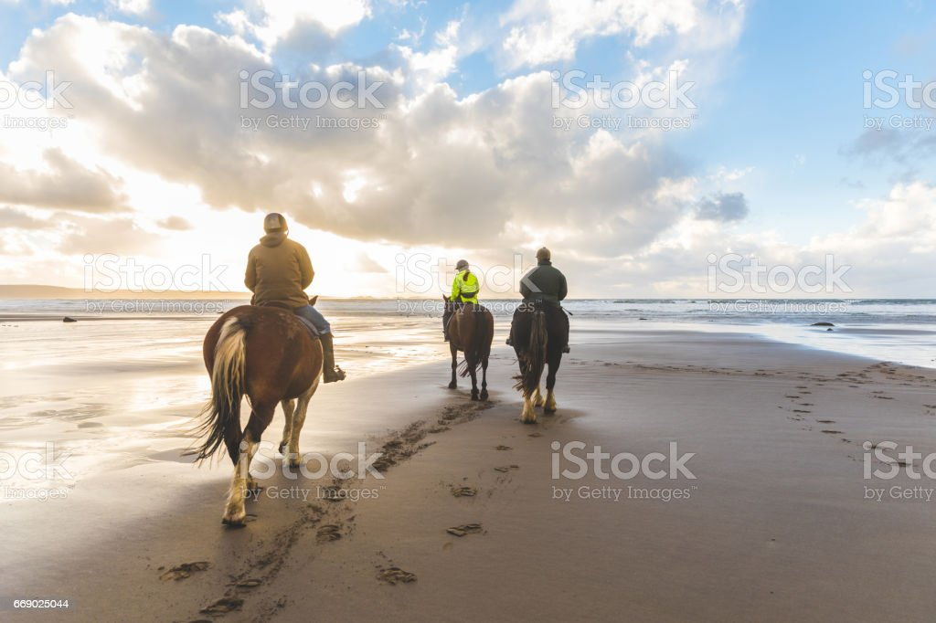 People horse riding on the beach stock photo