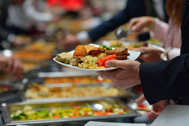 People in a buffet line with full plates people group catering buffet food indoor in luxury restaurant with meat colorful fruits  and vegetables buffet stock pictures, royalty-free photos & images