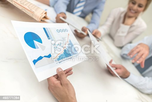 Group of people in a business meeting checking the market behaviour and holding a document with statistics and