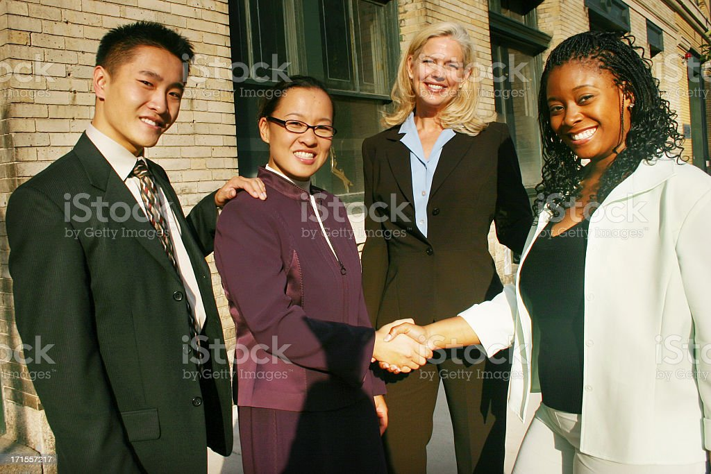 4 people in a business team shaking hands A diverse group of business people gather outside of their office building. A handshake between the two women signifies the close of a deal! Adult Stock Photo