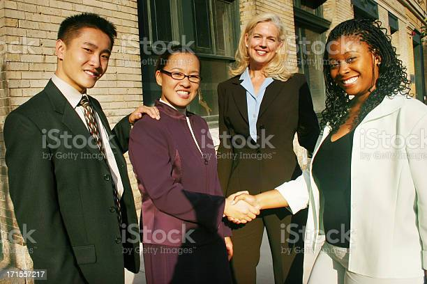 4 People In A Business Team Shaking Hands Stock Photo - Download Image Now