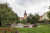 People in a city park and the New Town Hall in Prague