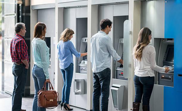 persone in fila a un bancomat - banca foto e immagini stock