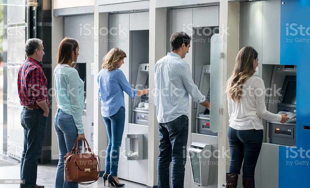 People in a line at an ATM stock photo