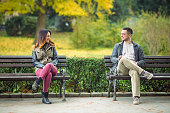 Two young people sitting on benches in a park and talking