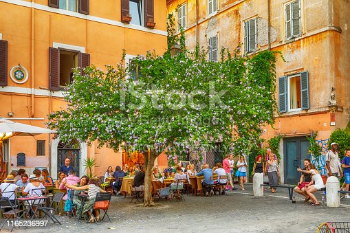 People sitting in a Restaurant in a Small Town Square in Trastevere, old town of Rome, Italy. Rome, Italy's capital, is a sprawling, cosmopolitan city with nearly 3,000 years of globally influential art, architecture and culture on display. Trastevere is one of Rome's most colorful areas. It's known for traditional and innovative trattorias, craft beer pubs and artisan shops.