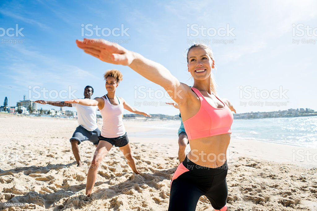 People in a yoga class at the beach stock photo