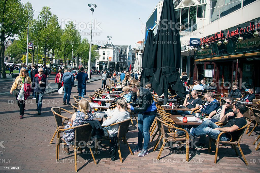 people in amsterdam enjoy sunny day on rembrandtplein stock photo