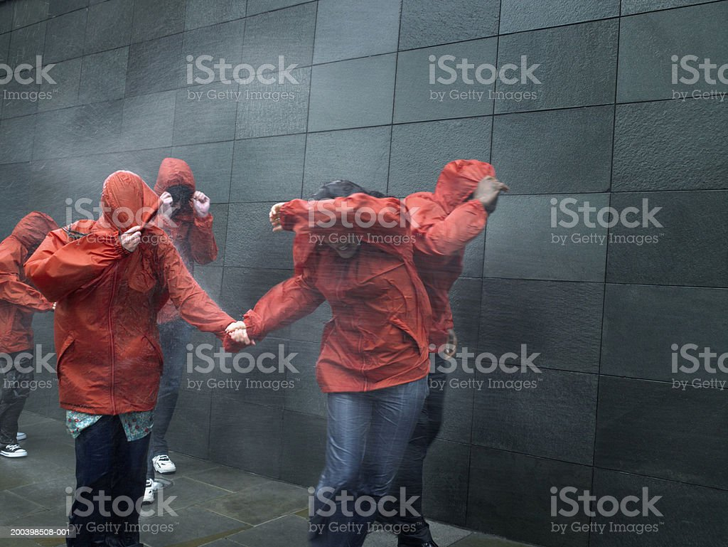 People in anoraks struggling against rainstorm, shielding faces stock photo