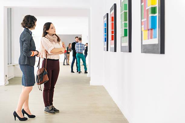 People In Art Gallery Looking At Artwork stock photo