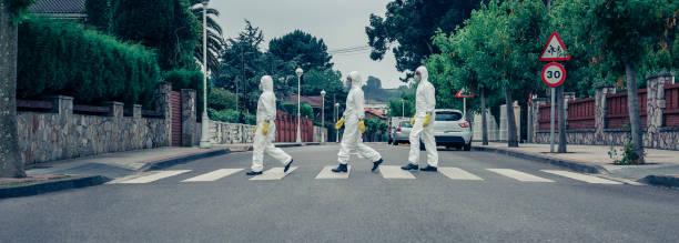 mensen in bacteriologische bescherming pakken die onderaan een lege straat lopen - avondklok stockfoto's en -beelden