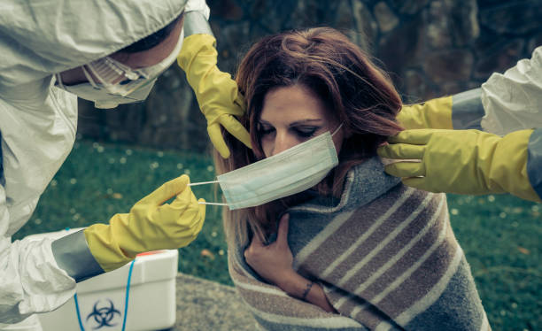 Menschen in bakteriologischen Schutzanzügen setzen eine Maske auf Frau – Foto