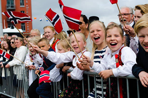 People in Bergen during Constitution Day 17th of May Bergen, Norway - May 17, 2016: People in Bergen, Norway during Constitution Day (17th of May). Adults and children are dressed up in traditional dresses (bunad) and waiving flags at the passing procession. norwegian culture stock pictures, royalty-free photos & images