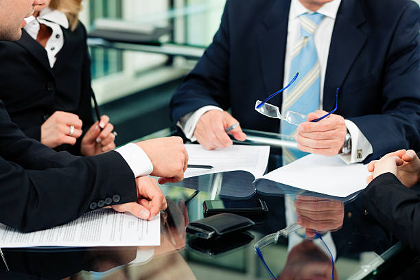 people in business suits with paperwork at desk - four lawyers stockfoto's en -beelden