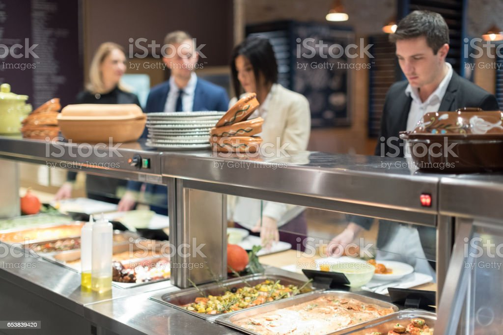 People in canteen waiting in line stock photo