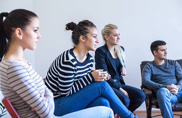 people in circle enjoying group therapy session - wellness seminar stock-fotos und bilder