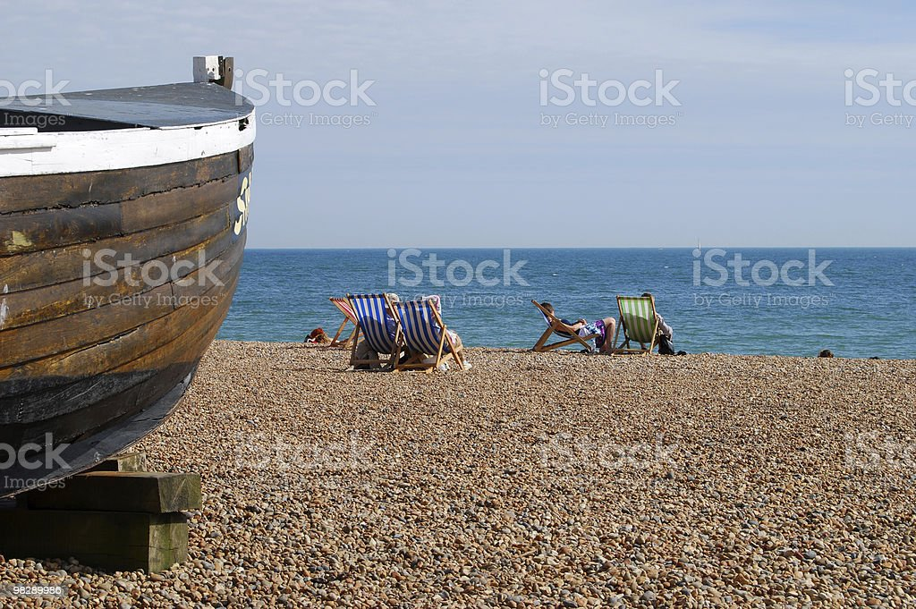 People in Deckchairs on Brighton Beach, East Sussex, England royalty-free stock photo