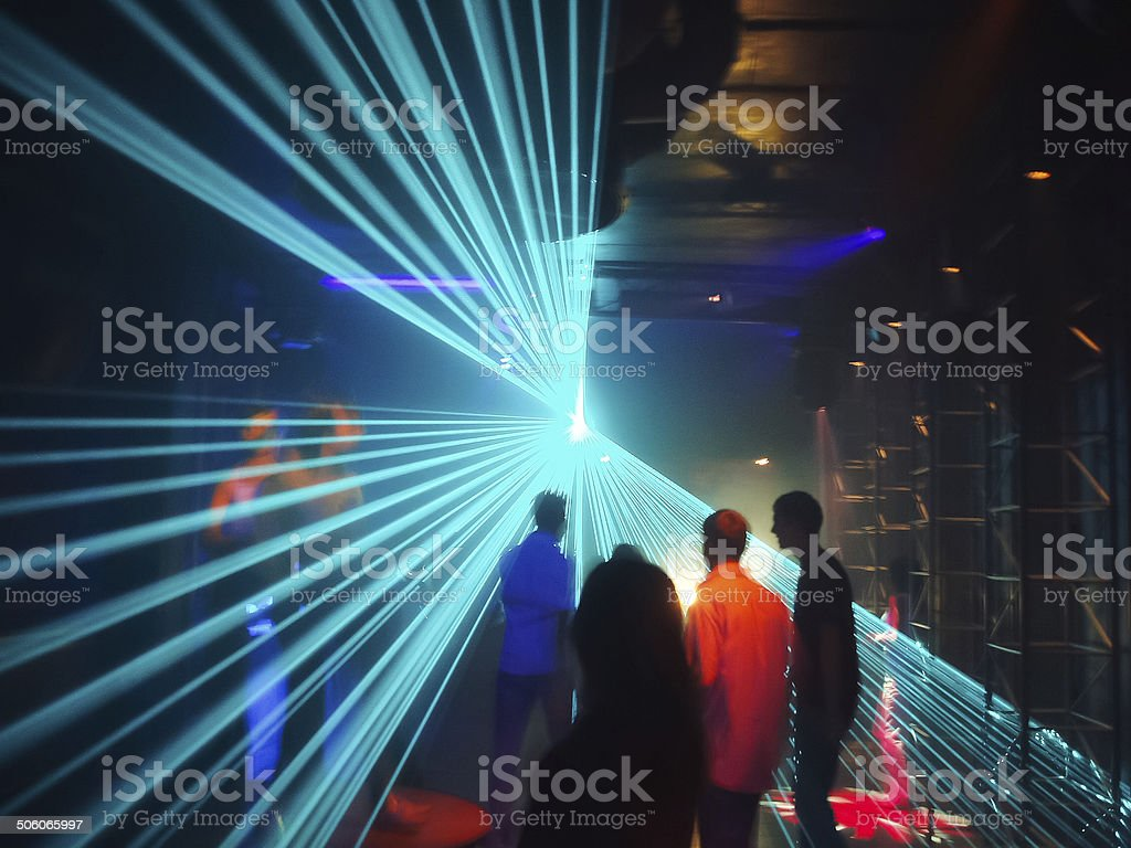 People in disco lightshow stock photo