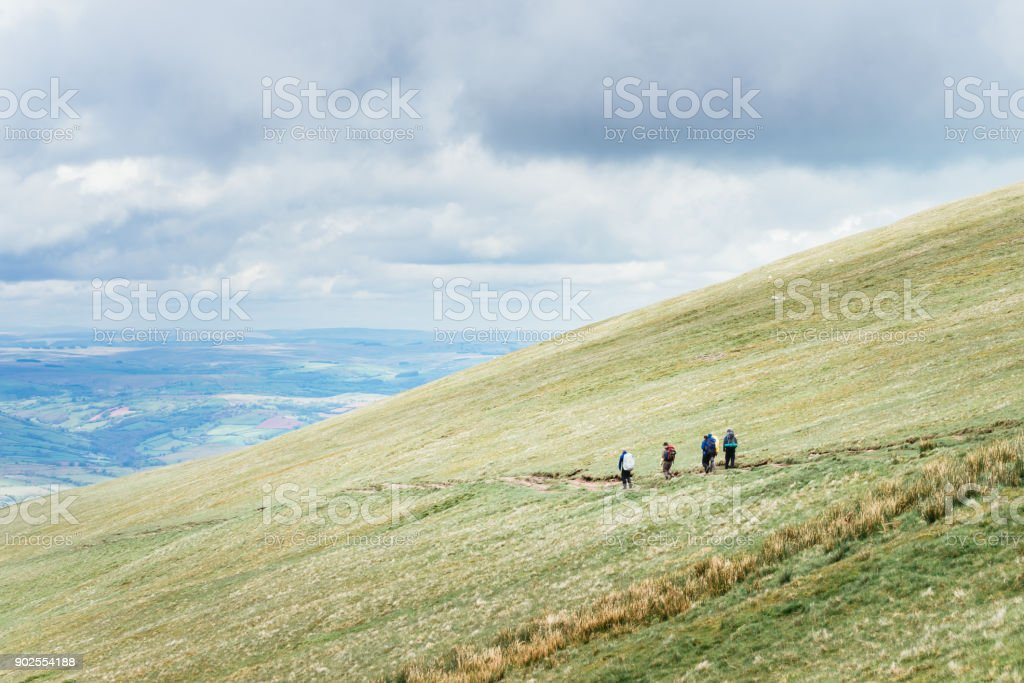 People in distance hiking on the hillside near to Pan Y Fan in Brecon Beacons, Wales stock photo