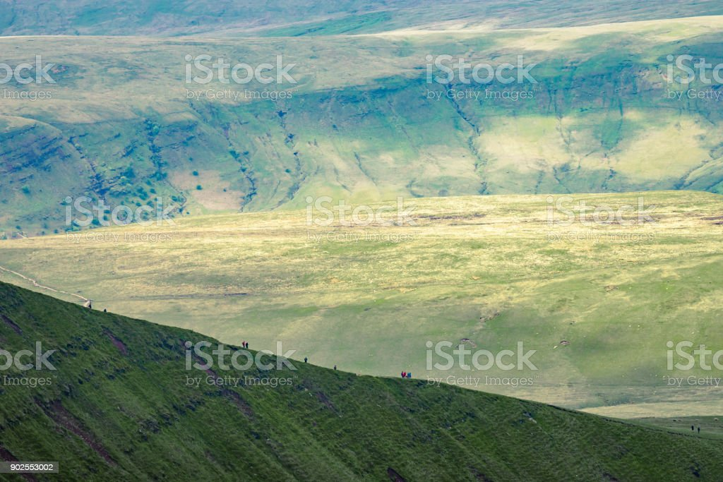 People in distance hiking up on the hillside near to Pan Y Fan in Brecon Beacons, Wales stock photo