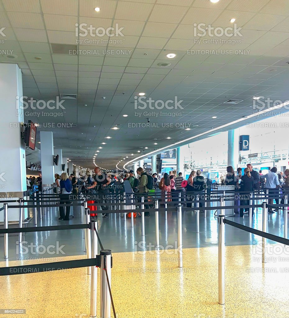 People in distance in airport queueing for tickets stock photo