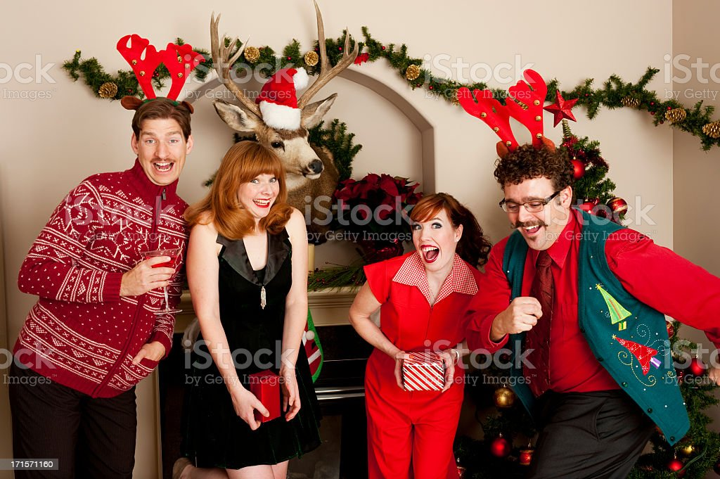 People in festive clothing smiling during a holiday party stock photo