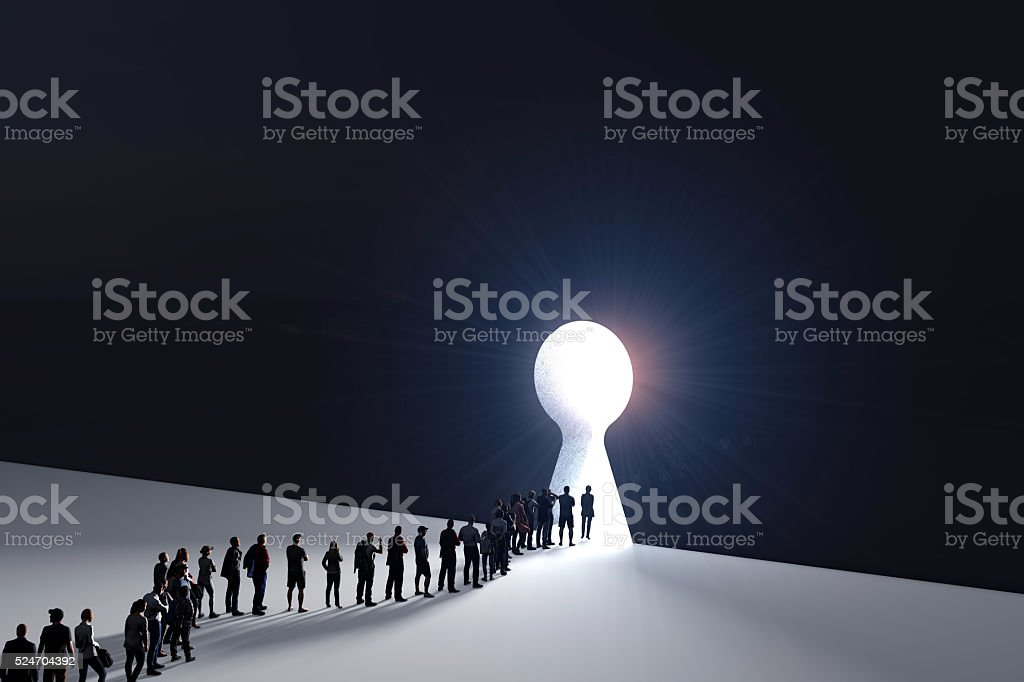 People in front of a bright keyhole opening stock photo