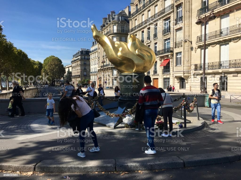 People in front of The Flame of liberty in Paris France stock photo