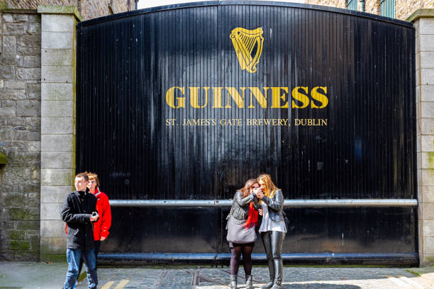 People in front of the old factory building wooden gate entrance at Guinness St. James´s Gate Brewery. stock photo