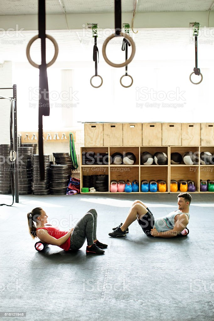 People in gym exercising with foam roller stock photo