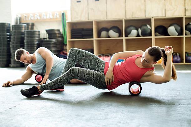 people in gym using support roller - masaje deportivo fotografías e imágenes de stock