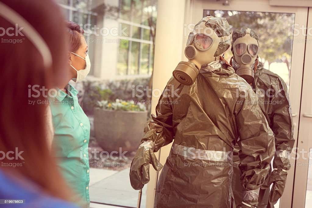 People in hazmat suits entering office for contagious outbreak stock photo
